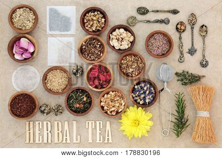 Herbal tea selection with wooden letters, metal strainer and tea bags on natural hemp paper background.