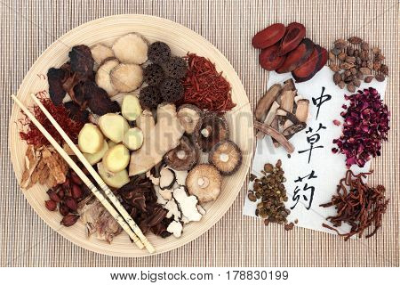 Chinese herb selection used in herbal medicine with chopsticks on a wooden bowl and calligraphy script on rice paper translated as chinese herbs.
