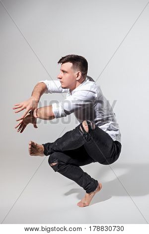 The young man dancing in contemporary stile of ballet at studio on gray