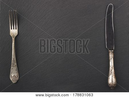 Melchior Spoon And Fork On The Black Stone Background