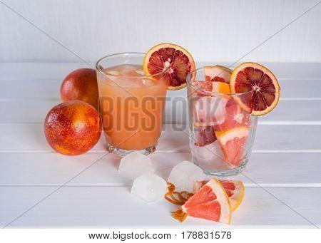 Full glass of grapefruit juice and glass of sliced fruit. Grapefruit sicilian orange with ice. White wooden background