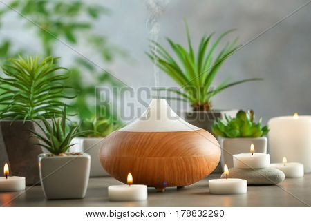 Aroma oil diffuser, candles and plants on table