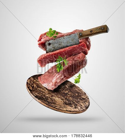 Flying pieces of raw beef steaks, with herbs, served on wooden board. Meat chopper cutting the flesh. Concept of food preparation in low gravity mode. Separated on smooth gray background