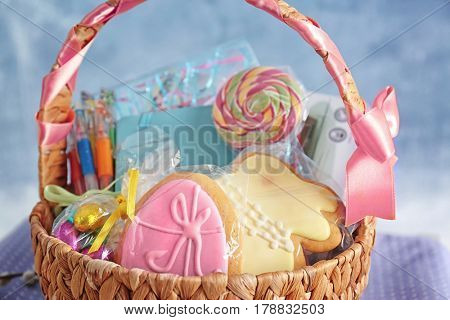 Easter basket with sweets and stationery on light background
