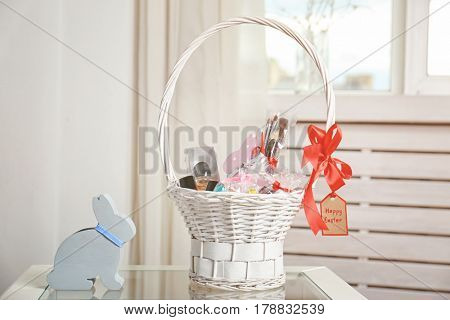 Easter basket with perfume, cosmetics and sweets on glass table