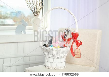 Easter basket with cosmetics, perfume and greeting card on light background