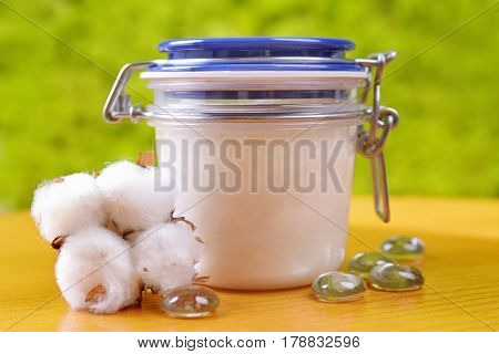 Jar with cosmetics on wooden table against blurred background