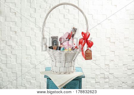 Easter basket with cosmetics, perfume, rabbit and sweets on light background