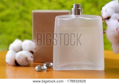 Bottle with perfume on wooden table against blurred background