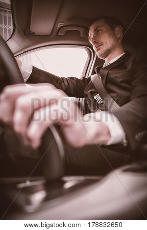 Handsome businessman on drivers seat in his car