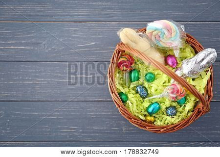 Traditional Easter basket with colorful lollipops and chocolate eggs on wooden background