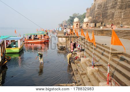 Maheshwar India - 3 February 2015: People washing clothes on sacred river Narmada ghats. To Hindus Narmada is one of 5 holy rivers of India