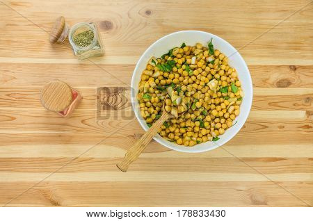 Chick peas in large bowl. Top view of cheak peas in wood spoon on the table and bowl of raw chicklings