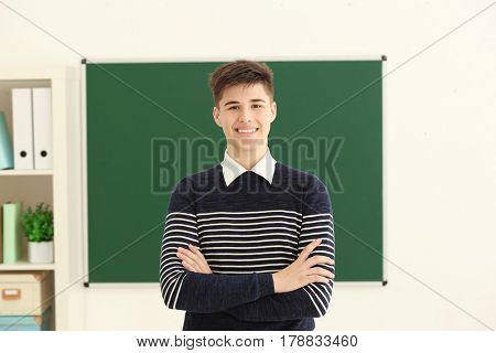 Smiling schoolboy with crossed arms standing on blackboard background