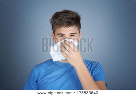Young man blowing nose on tissue against color background