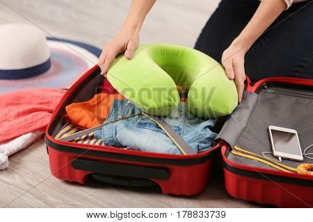 Young woman packing travel pillow into suitcase while sitting on floor at home