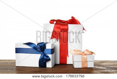 Beautiful white gift boxes with satin ribbons on wooden table