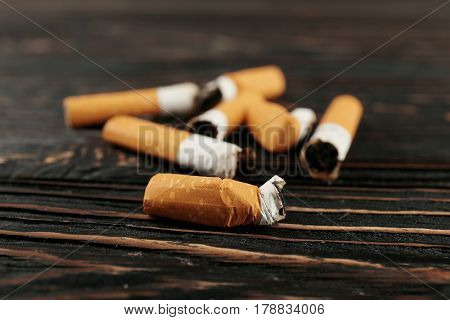 Cigarette butts on wooden background