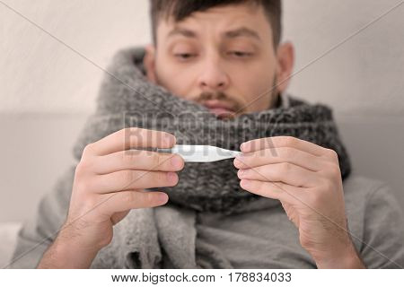 Young ill man measuring temperature at home