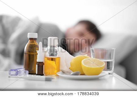 Set of medicines and lemons with blurred ill man on background