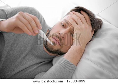 Young ill man measuring temperature while lying in bed at home