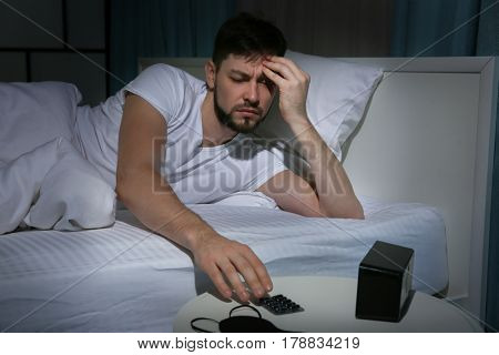 Handsome young man going to take pills against headache while lying in bed at night