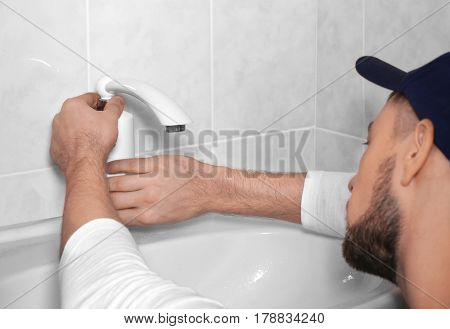 Closeup of plumber fixing tap on sink