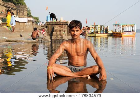 Young Man Sitting On Sacred River Narmada At Maheshwar