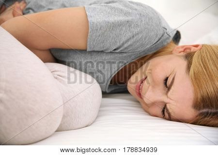 Young woman suffering from pain on bed