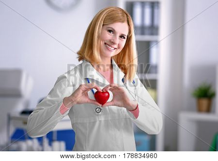 Female doctor with stethoscope holding heart, on blurred background