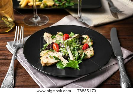 Delicious dinner with chicken, arugula, spinach and basil on black plate