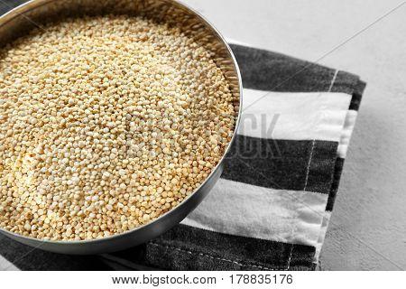 Organic quinoa seeds in bowl on striped napkin