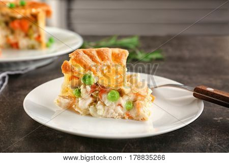 Plate with piece of delicious chicken pot pie on kitchen table