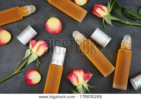 Bottles with perfume and rosebuds on grunge background