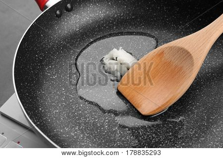 Wooden spoon with coconut oil on frying pan