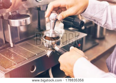 Graphic image of flare against cropped hands of barista making cup of coffee