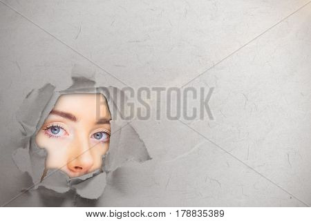 Close up of woman face against circle hole in paper 3d
