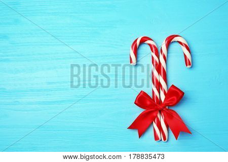 Christmas candy canes on color wooden  background