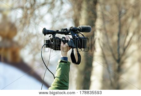 Professional camcorder in male hand outdoors