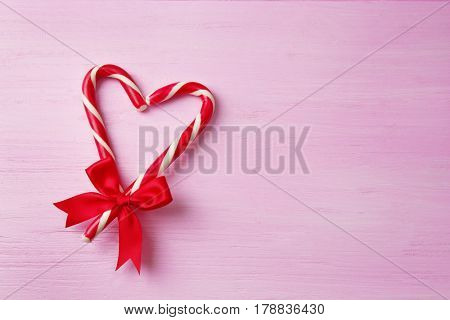 Heart shape made with candy canes on color wooden background