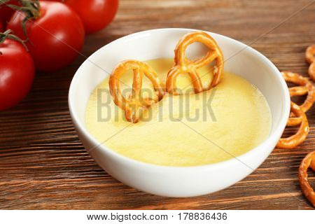 Dipping pretzel into bowl with cheese sauce on dining table