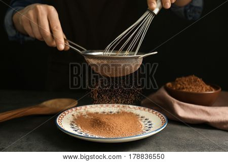 Female hands with sieve and corolla powdering cocoa onto plate