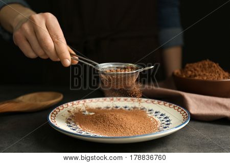 Female hand with sieve powdering cocoa onto plate