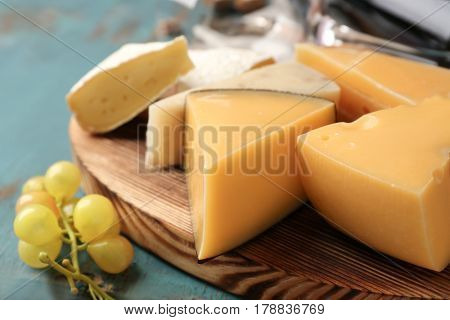 Assortment of cheese on wooden board, closeup