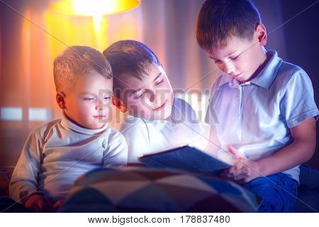 Three kids using tablet pc in bedroom at night. Brothers with tablet computer in a dark room. Children little boys watching movie together. Bedtime