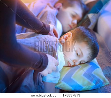 Children sleeping and dreaming in bed, Mother cover her little sons with a blanket. Mothering. Childhood and parenthood concept, warm and healthcare. Bedtime