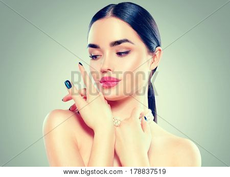 Beauty Fashion Model Woman touching her face. Portrait with perfect skin. Pink Lips, Beautiful Sexy Brunette Girl with Luxury Makeup and Manicure.