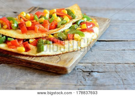 Stuffed vegetable omelet on wooden board. Fried omelet stuffed with red and green bell peppers and canned corn. Breakfast eggs recipe. Rustic style. Closeup