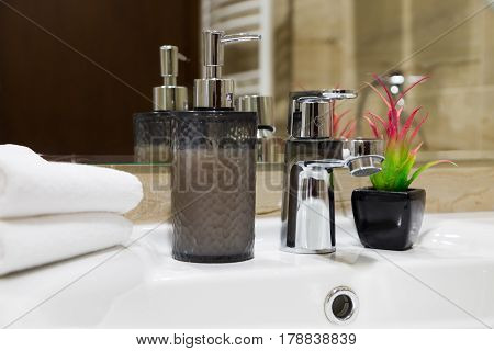 Stylish liquid soap pump and potted flowering plant on a white hand basin with clean towels in a hotel or home close up view