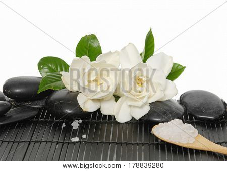 Set of with stones and salt in spoon ,gardenia on bamboo mat